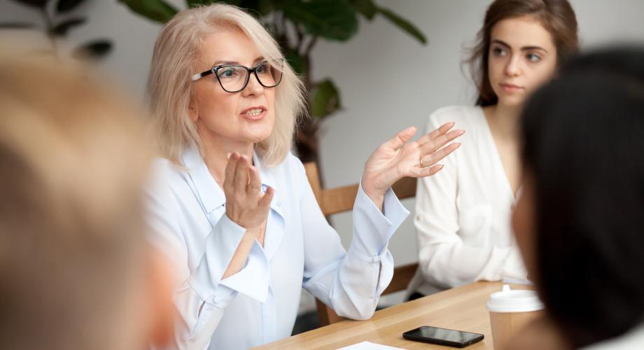Dojrzała kobieta prowadzi warsztaty w grupie