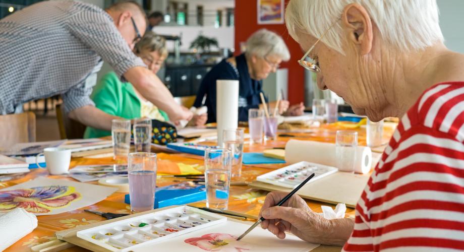 Seniorzy w grupie biorą udział w zajęciach aktywizujących