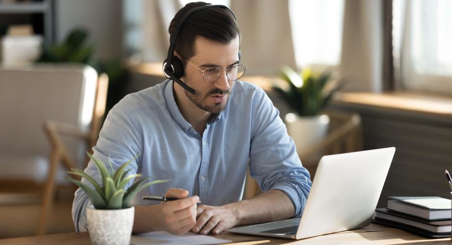 Mężczyzna z zestawem słuchawkowym, patrzący na ekran, oglądający szkolenie internetowe